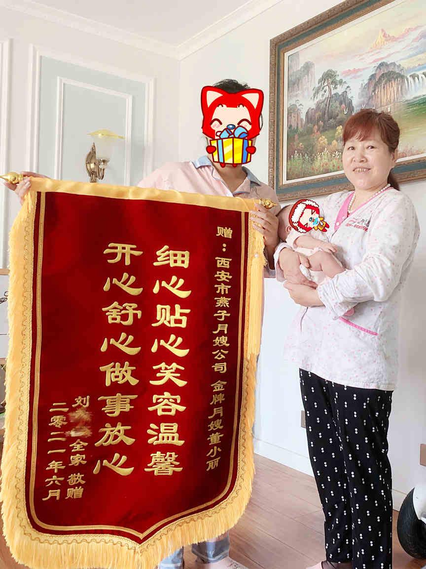 西安燕子月嫂金牌五星月嫂董小丽抱着宝宝与她的客户手持锦旗合影